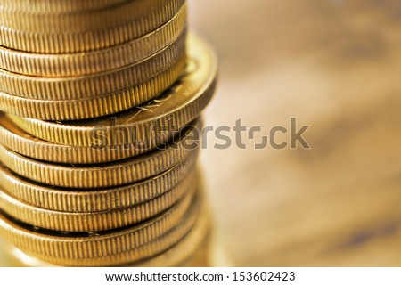 Pile of golden coins with copy space on the right. - stock photo
