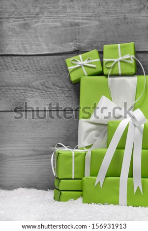 Pile of green Christmas presents, with snow on grey wooden background - stock photo