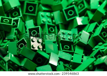 Pile of green color building blocks with selective focus and highlight on one particular block using available light. - stock photo