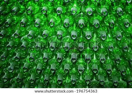 Pile of green wine bottles forming a wall. - stock photo