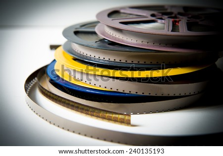 Pile of grey, blue, yellow and purple 8mm super8 movie reels on white background, vintage look and color effect - stock photo