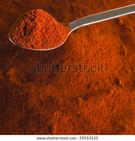 Pile of heaped chili powder with silver tea spoon - stock photo