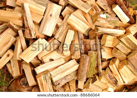 Pile of heavy wood logs for winter heating stacked outdoors - stock photo