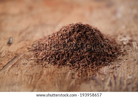 pile of hot chocolate flakes  on wooden background, shallow DOF - stock photo