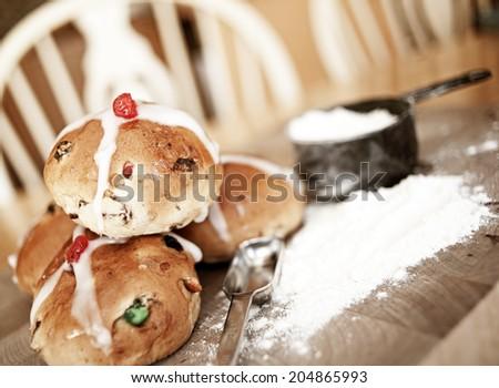 Pile of hot cross buns and flour - stock photo