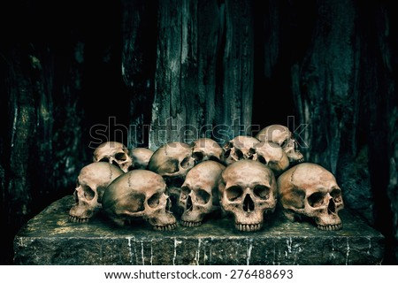 Pile of human skulls on stone table for sacrifice with golden and candle wax - stock photo