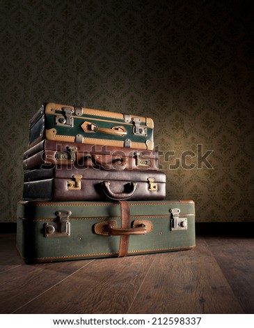 Pile of leather vintage suitcases, retro wallpaper on background. - stock photo