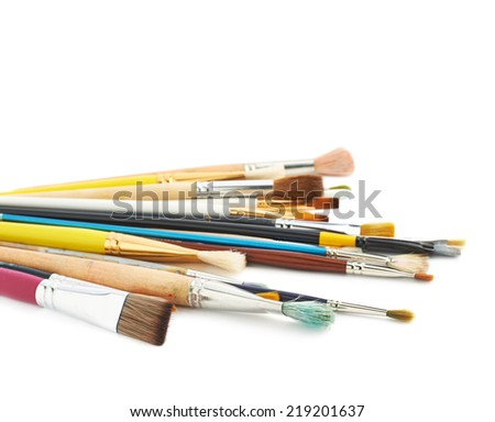 Pile of multiple different size and shape painting brushes isolated over the white background - stock photo