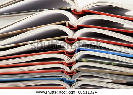 pile of new book with bending pages on white background - stock photo