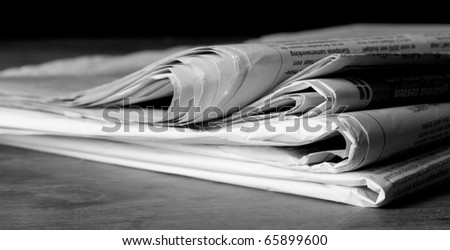 Pile of newspapers desaturated - stock photo