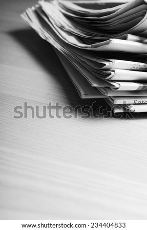 Pile of newspapers on wooden surface - stock photo