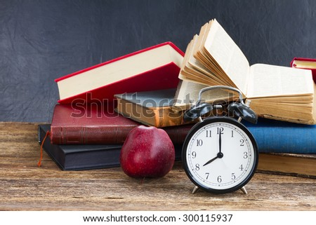 pile of  old books with antique alarm clock  and apple on wooden shelf - stock photo