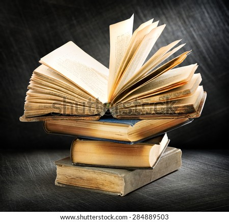 Pile of old books with one open on top - stock photo