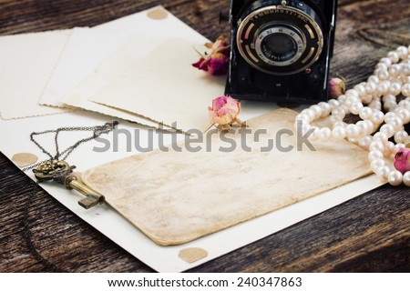 pile of old empty photos and papers  with key and  vintage camera - stock photo