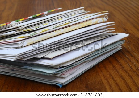 Pile of old mails letters and envelopes on wooden table - stock photo