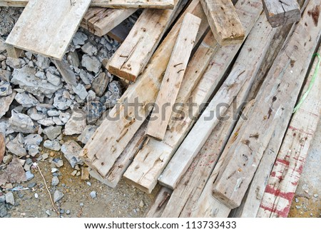 Pile of old used timber in construction site - stock photo