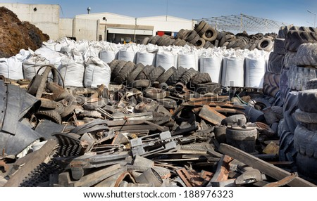 Pile of old used tires and different garbage stocked for recycling - stock photo