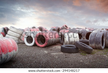 Pile of old used tires stocked background with dramatic sky - stock photo