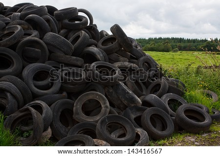 Pile of old vehicle tires dumped in the countryside by farmer - stock photo