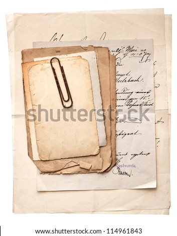 pile of old vintage papers, cards and letters with paper clip on white background - stock photo