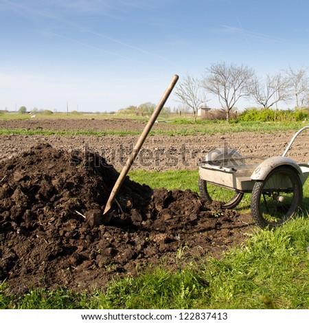 pile of organic fertilizer near to the vegetable garden - stock photo