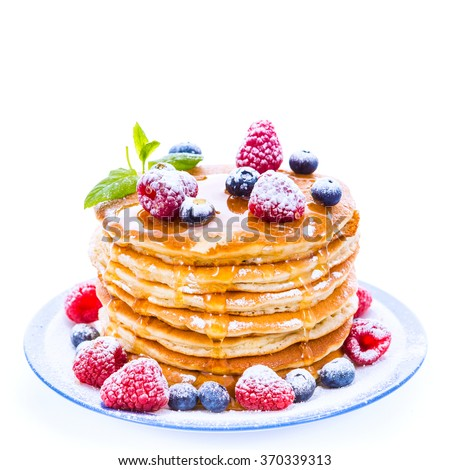 Pile of pancakes with blueberries and raspberries sprinkled with icing sugar and poured on with honey for breakfast on white background - stock photo