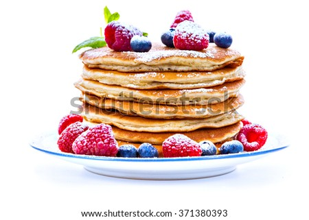 Pile of pancakes with blueberries and raspberries sprinkled with icing sugar for breakfast on white background - stock photo