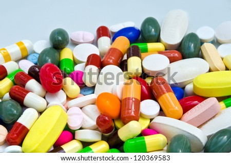 Pile of pills on white dish - stock photo