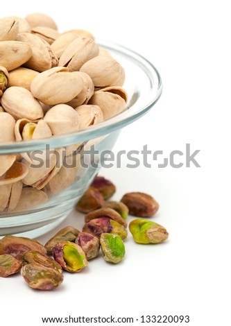 pile of pistachio nuts in a glass bowl on white background - stock photo