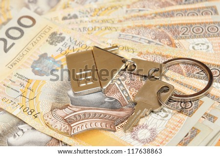 Pile of Polish money and a key for the house - stock photo
