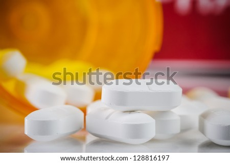 pile of prescription pills with pill bottle in the background - stock photo