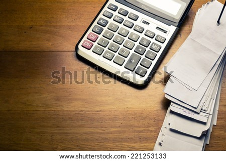 Pile of receipts and calculator on wood table - stock photo