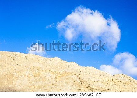 Pile of sand and blue sky with white clouds over it. - stock photo
