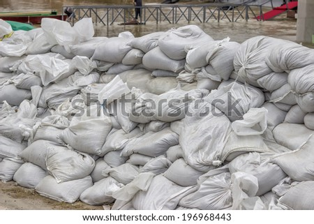pile of sandbags for flood defense and river in background - stock photo