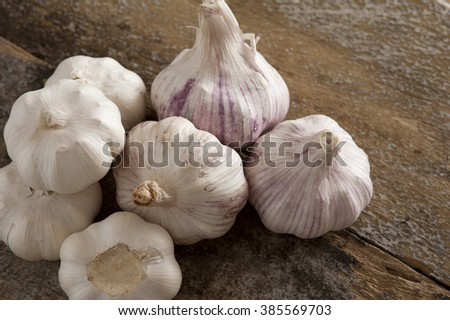 Pile of seven whole white and purple garlic bulbs on old wooden table ready to break apart and eat - stock photo