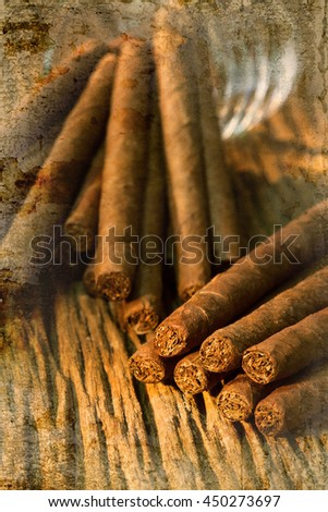 pile of small cigar on old wooden table overlap with old wall textured background. retro filter. - stock photo