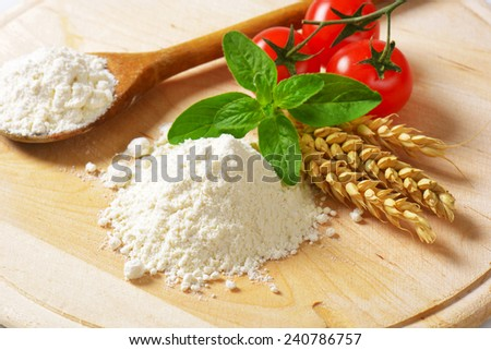 Pile of soft wheat flour, wooden spoon and fresh tomatoes on round cutting board - stock photo