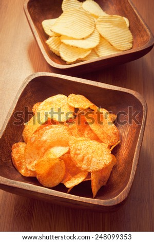 pile of spicy slices of salty chips in a wood bowl  - stock photo