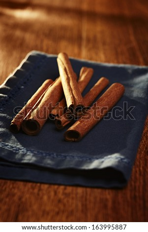 Pile of stick cinnamon on a napkin viewed from the end to show the rolled bark on a wooden table with shallow dof - stock photo