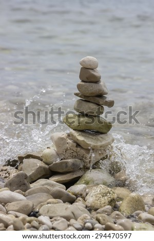 Pile of stones in the balance on sea coast with sea wave in the background. Concept of stability, balance and harmony.  - stock photo