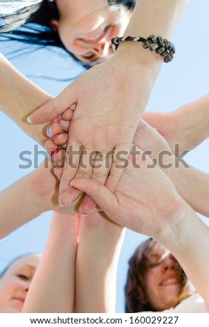 Pile of teen friends hands symbol of teamwork on blue sky background - stock photo