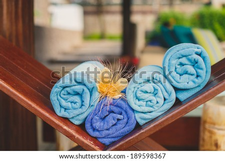 Pile of towels at the swimming pool of a tropical resort - stock photo