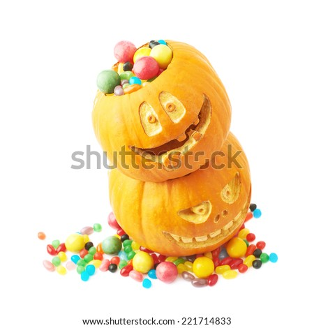 Pile of two Jack o lantern Halloween pumpkins filled with multiple colorful sweets and candies, composition isolated over the white background - stock photo