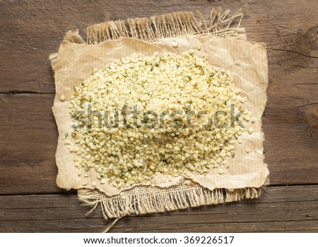 Pile of Uncooked Hemp seeds on wood close up - stock photo