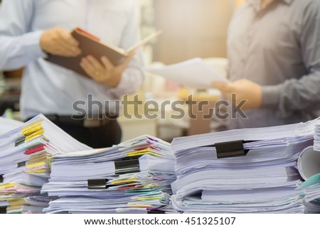 Pile of unfinished documents on office desk with businessman background - stock photo