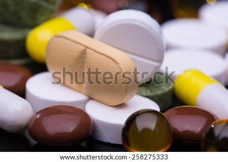 Pile of various colorful pills isolated on black - stock photo