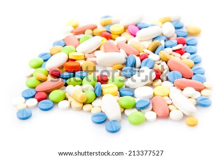 Pile of various colorful pills isolated on white - stock photo
