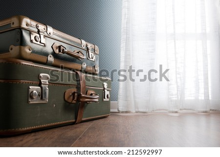 Pile of vintage suitcases next to a window on hardwood floor. - stock photo