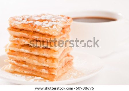 Pile of waffles with honey and sugar and coffee on white background - stock photo