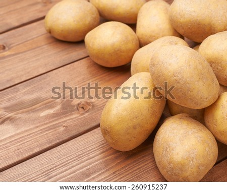 Pile of washed fresh potatoes lying over the wooden table's surface as a background composition - stock photo
